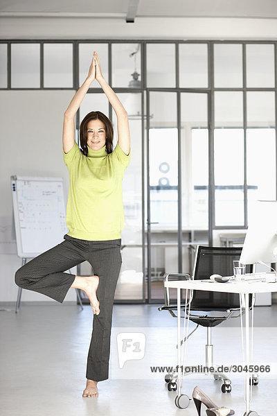 Geschäftsfrau macht Yoga in office