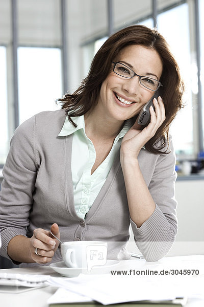 portrait of businesswoman sitting at desk talking on telephone