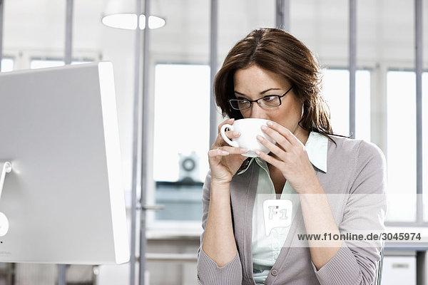 Porträt von Geschäftsfrau sitzt vor Computer Kaffeetrinken