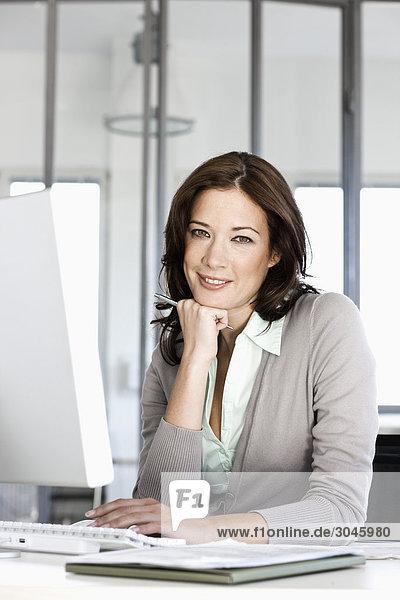 Porträt von geschäftsfrau an Computer Schreibtisch sitzen