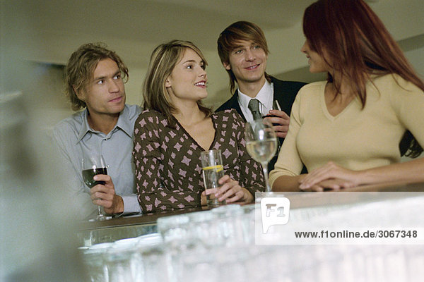 Young woman talking with friends at bar