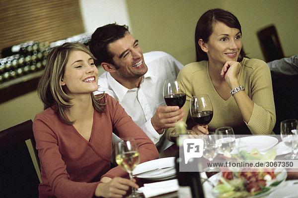 Wein trinkender Mann mit Frauen am Restauranttisch