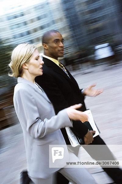 Geschäftsmann und Geschäftsfrau gehen zusammen im Gespräch