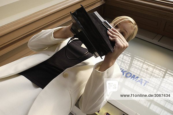 Well dressed woman looking through purse  low angle view