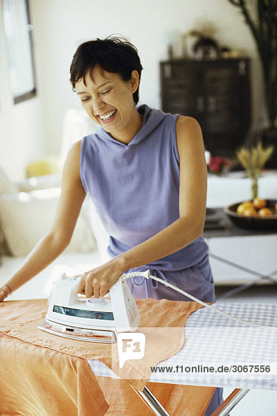 Woman doing ironing and laughing