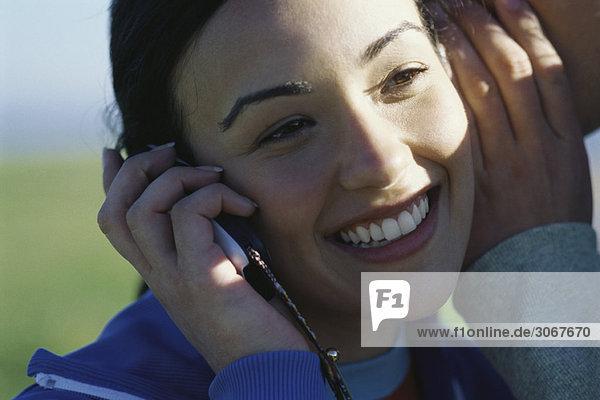Junge Frau mit Handy  Mann flüstert ihr ins Ohr