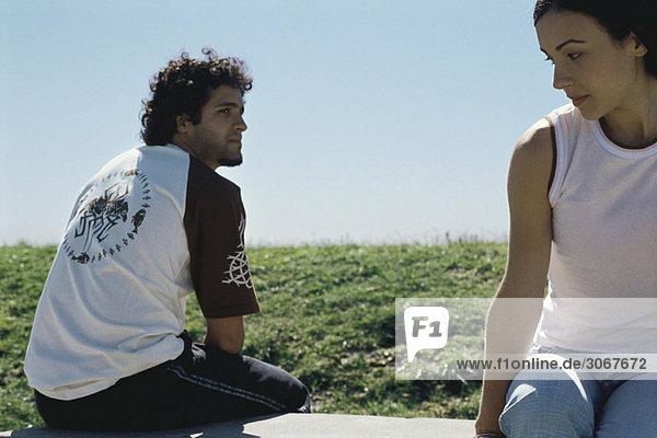 Junges Paar auf der Parkbank sitzend  über die Schultern blickend