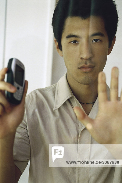 Man pressing hand against window  holding cell phone  looking at camera