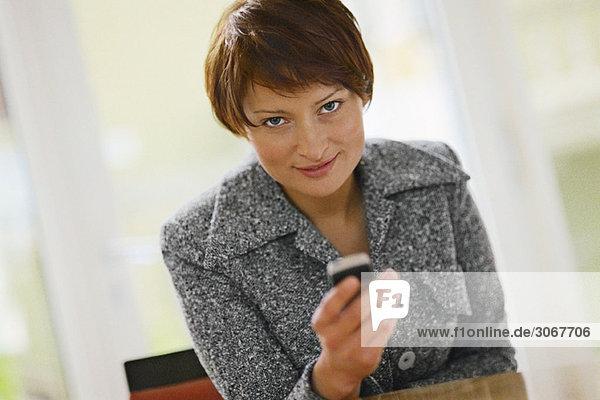 Geschäftsfrau mit Handy  lächelnd in der Kamera