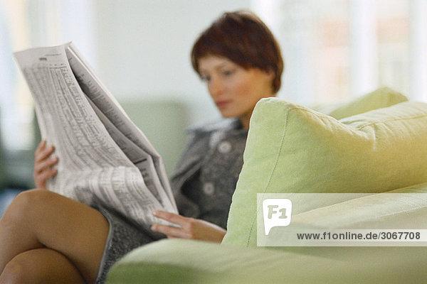 Geschäftsfrau auf dem Sofa sitzend Zeitung lesen