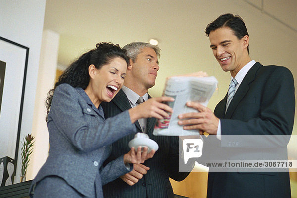 Gruppe von Führungskräften  die Zeitung anschauen und lachen
