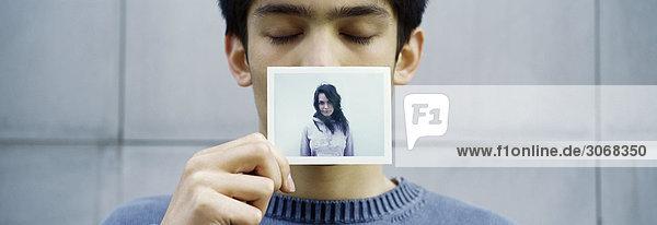 Mann hält Bild der Freundin vor dem Gesicht  Augen geschlossen