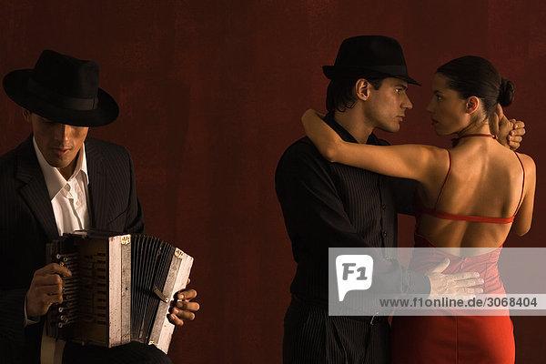 Pärchen tanzen zusammen mit einem Akkordeonspieler