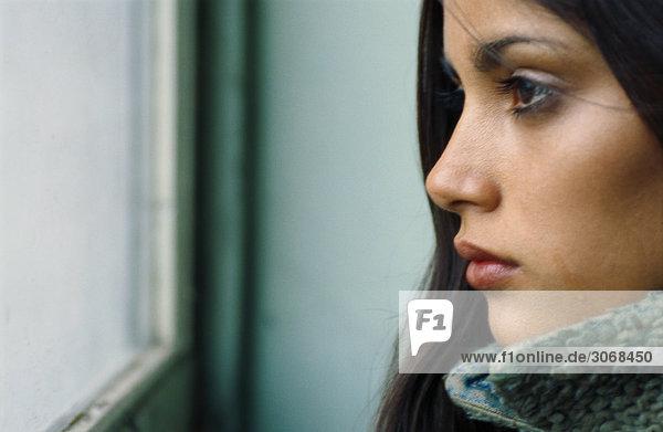 Junge Frau schaut aus dem Fenster  weint  Profil