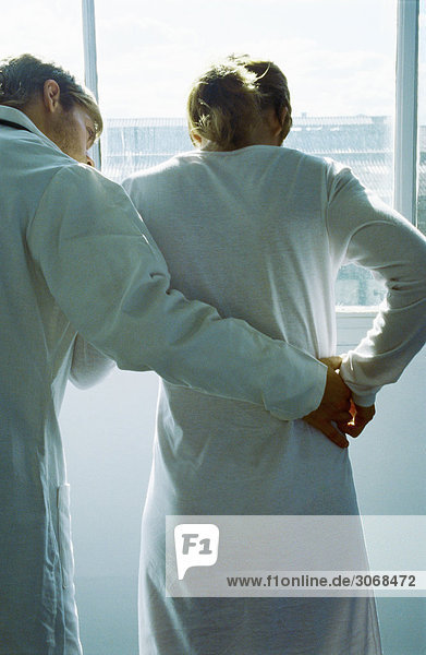 Arzt hilft Patientin beim Gehen  Rückansicht