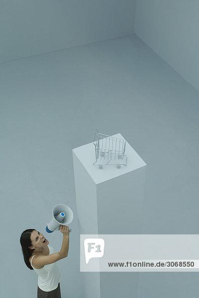 Frau steht neben einem hohen Sockel mit Einkaufswagen oben drauf und schreit ins Megaphon.