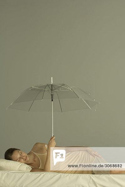 Frau im Bett liegend mit geschlossenen Augen  Schirm hochhaltend