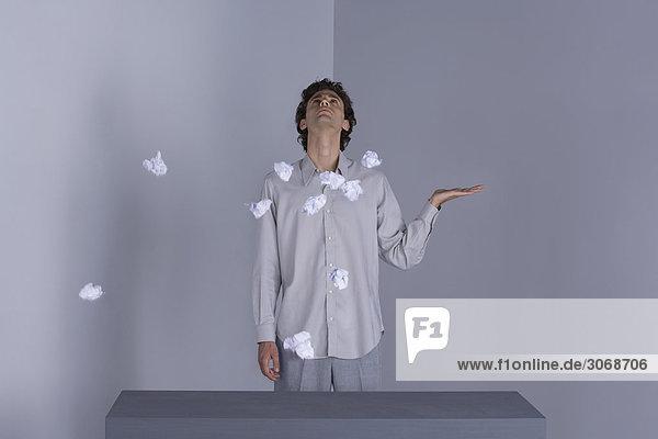 Mann steht mit ausgestreckter Hand  schaut nach oben  Papierkugeln in der Luft um ihn herum.
