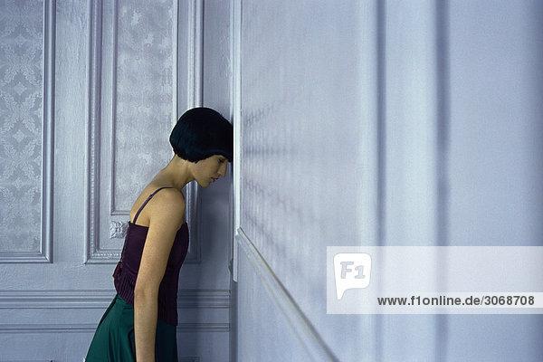 Frau in Ecke stehen, lehnend Kopf gegen die Wand, Augen