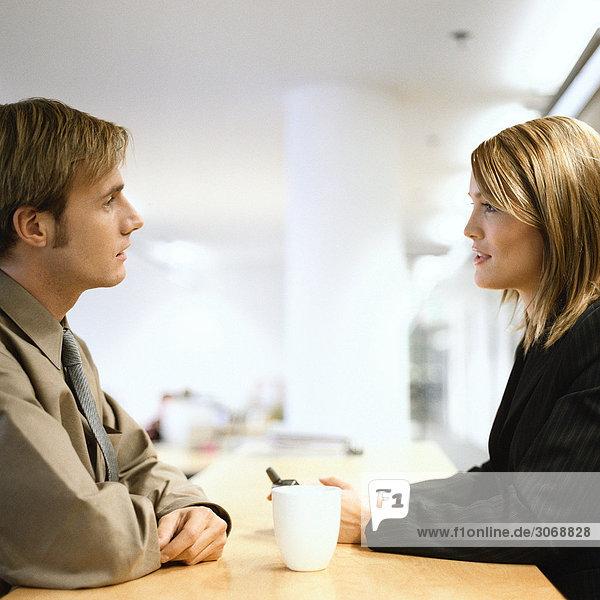 Mann und Frau sitzen von Angesicht zu Angesicht am Tisch und trinken Kaffee