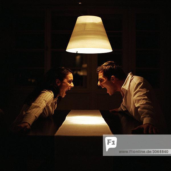 Mann und Frau stehen sich bei Tisch gegenüber und schreien sich an.