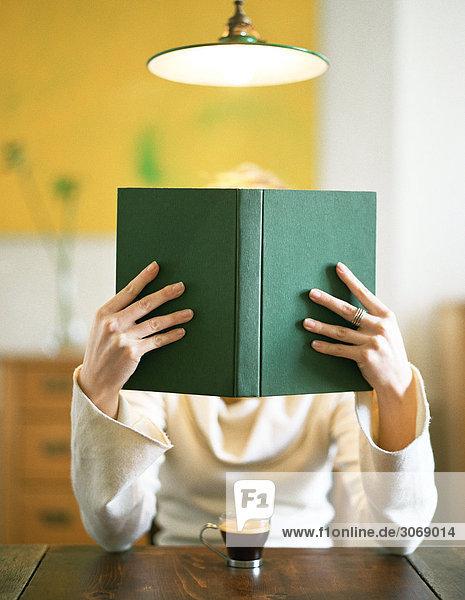 Frau sitzt am Tisch und liest Buch