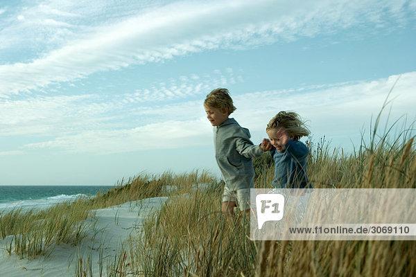 Boy and girl running through dune grass  holding hands