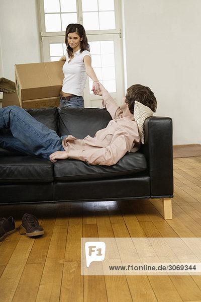 Junges Paar beim Umziehen  Mann auf Sofa  Frau mit Karton zieht ihn hoch