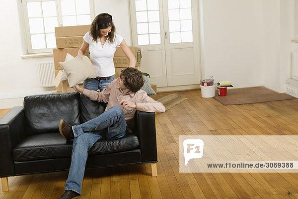 Junges Paar beim Umzug  Kissenschlacht auf Sofa