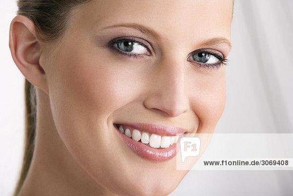 Junge Frau mit zurückgebundenen Haaren lächelt in Kamera  Nahaufnahme