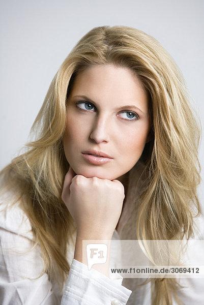 Junge Frau mit langen blonden Haaren  Kopf auf Hand gestützt  Portät