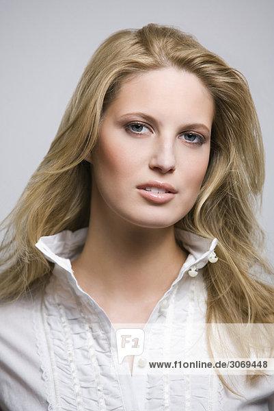 Junge Frau mit weißer Bluse und langen blonden Haaren  Portät