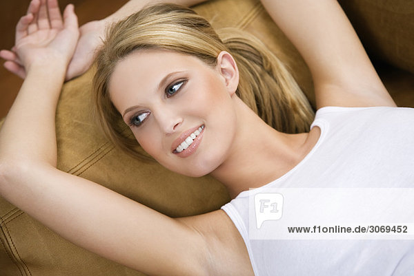 Junge Frau liegt auf braunem Sofa  Porträt