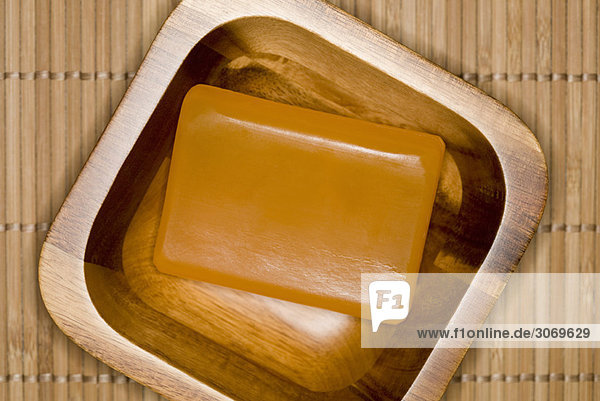 Close up of bar of soap in wooden bowl RLX-112036