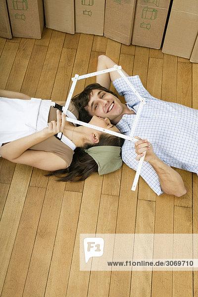Junges Paar vor Umzugskartons sieht durch Meterstab als Haus  von oben