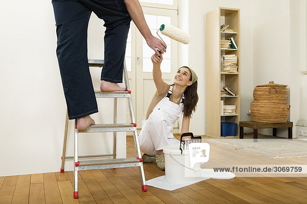 mann auf leiter in wohnung beim streichen frau reicht. Black Bedroom Furniture Sets. Home Design Ideas