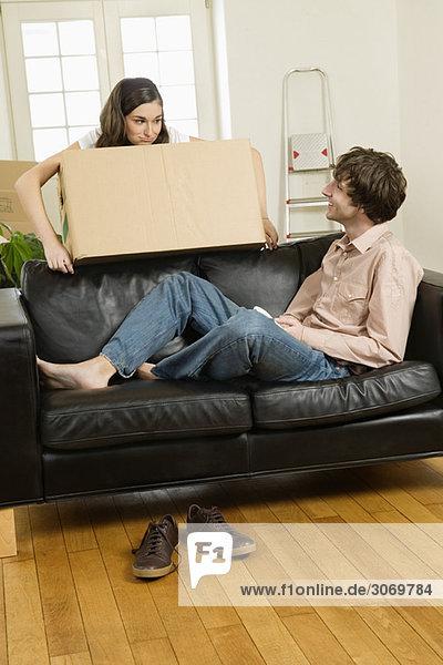 Junges Paar beim Umzug  Mann liegt auf Sofa  Frau trägt Karton