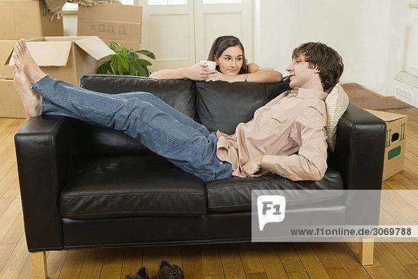 Junges Paar beim Umziehen  machen Pause  Mann liegt auf Sofa