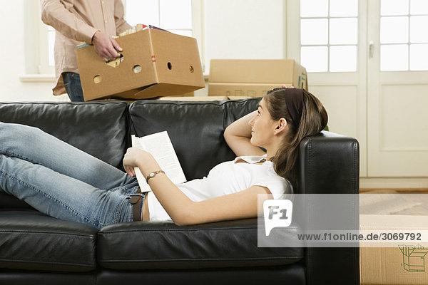 Junges Paar beim Umzug  Frau liegt auf Sofa  Mann trägt Karton