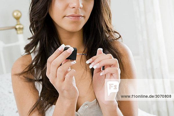 Junge Frau malt Fingernägel