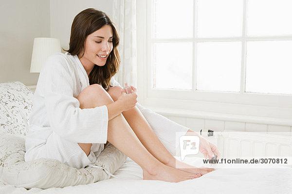 Junge Frau malt Zehennägel