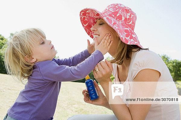 Mädchen legt Sonnencreme auf Mutter