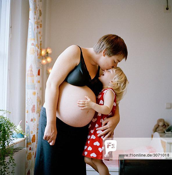 Frau küssen Schwangerschaft Tochter
