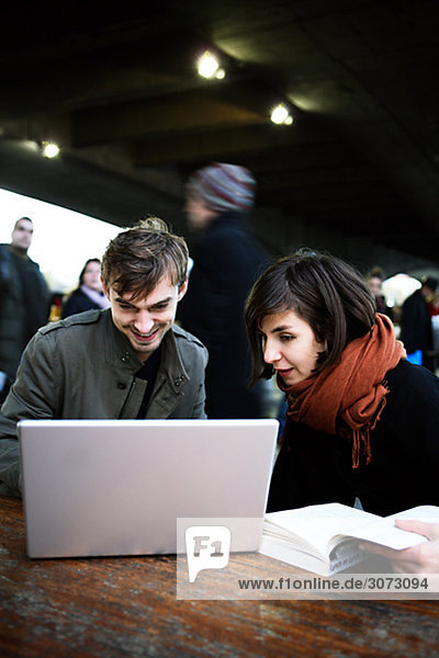 A couple in London using a laptop Great Britain.