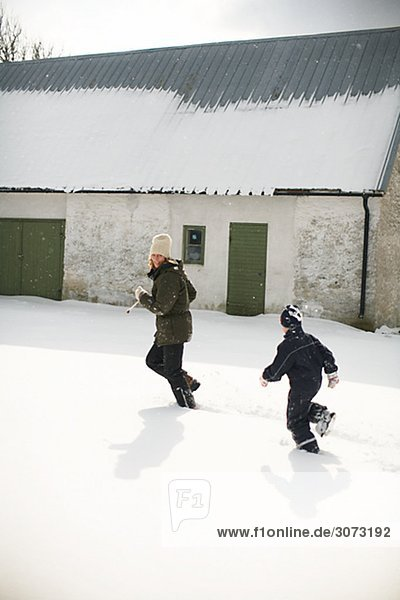 Mother and boy playing in the snow Gotland Sweden.