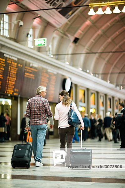 A couple with suitcases at a railway station Sweden.