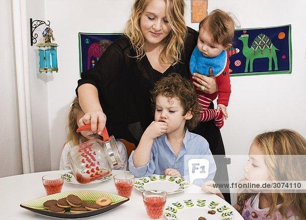 Mutter Ausgießen von Obst trinken nach ihrer Kinder-Schweden.