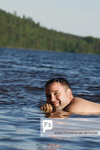 Ein lächelnd mann nehmen ein erfrischendes Bad im Meer Östergötlands Schweden.