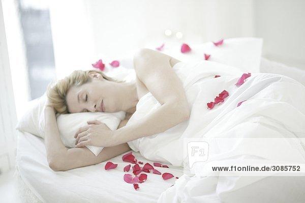 Eine Frau schlafen umgeben von Rosenblüten