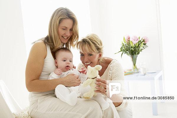 Baby sitzt auf Mutter Knie  Großmutter hält Kuscheltier
